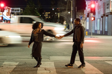 Couple holding hands on pedestrian crossing, Los Angeles, California, USA