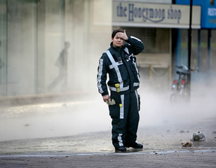 Fire fighter takes a break in the street after a pipe from Rotterdam city's heating system broke in the city centre