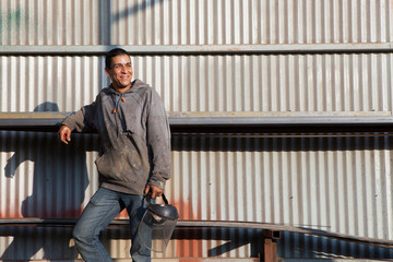 Builders leaning against corrugated building looking away smiling