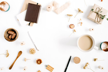 Blogger or freelancer workspace frame of coffee mug, notebook, sweets and accessories on white background. Flat lay, top view minimalistic brown styled home office desk. Beauty blog concept.