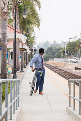Young businessman cyclist looking back from rail station platform