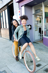 Female barber partners having fun on bicycle outside barber shop