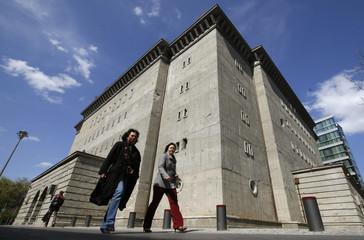 Pedestrians walk past a former World War Two bunker in Berlin