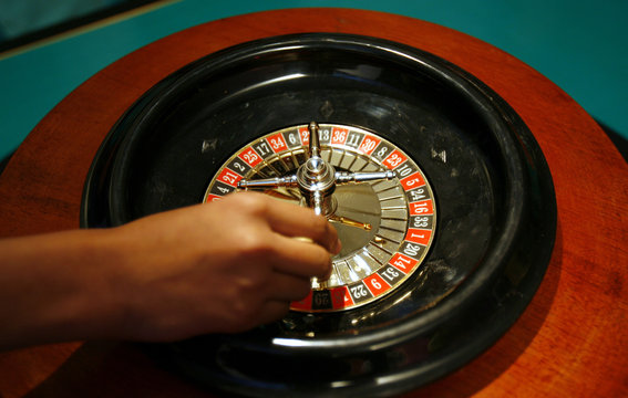 """A dealer spins a roulette wheel at a mock casino during the launch ceremony of """"Ten Hotels"""" by Dawnay Day in New Delhi"""