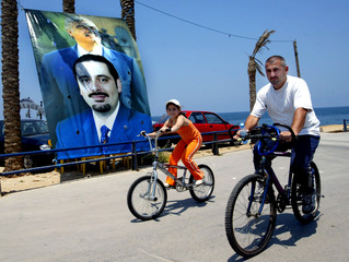 A Lebanese man and his daughter ride their bicycles at the seafront near a huge poster of slain ...