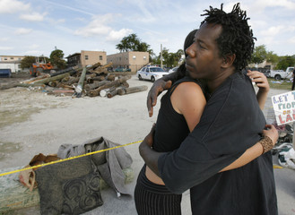 """Jimmy Alvin is comforted by supporter Monique Moyer the day after a fire destroyed """"Umoja Village"""" shantytown in the Liberty City section of Miami"""