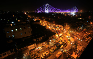 Traffic moves during the evening as the Howrah Bridge is lit up in the background in the eastern Indian city of Kolkata