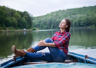 relaxed girl sitting in a boat on a lake