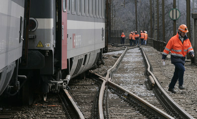 A worker walks next to a derailed train of the Swiss Federal Railways in Lavorgo