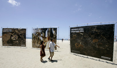 Residents of Rio walk near giant pictures during Greenpeace's protest against destruction of Amazon rainforest, at Copacana beach in Rio de Janeiro