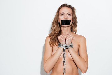 Naked young caucasian woman standing in chain over white wall