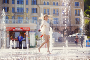 Young girl in a light dress is having fun in a fountain on the background of a sunny city