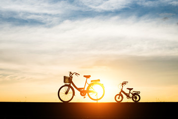Silhouette, two bikes with sunset.