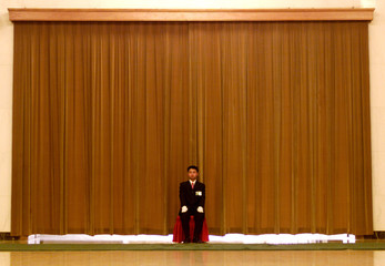 A SECURITY GUARD IS POSTED IN FRONT OF AN ENTRANCE IN THE GREAT HALL OF THE PEOPLE IN BEIJING.