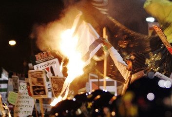 Pro-Palestinian demonstrator burns Israeli flag during protest near Israeli embassy in London