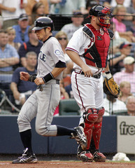 Seattle Mariners runner Suzuki runs past Atlanta Braves catcher McCann after scoring a run in the first inning during their MLB interleague baseball game in Atlanta