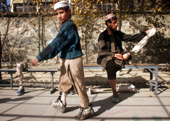 Afghan landmines victims try their new artificial legs in the Red Cross hospital in Kabul November 2..