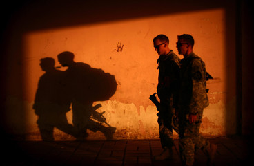 U.S. soldiers walk in a government centre, southeast of Baghdad