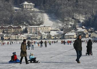 People enjoy the frozen Lac de Joux at Le Pont in the Jura region in Western Switzerland