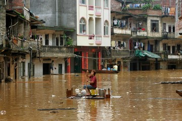 A Chinese woman makes her way in a flooded street.