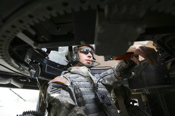A U.S soldier of 64th Armor Regiment sits in the turret of a Humvee during patrol in the predominantly Shi'ite neighbourhood of al-Washash in Baghdad