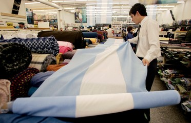 An Argentine man displays a fabric with the colors of the Argentine flag at a store in Puerto Madryn