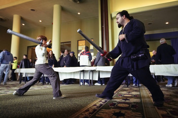 A convention goer spars with a man dressed as a fantasy fighter at the Hotel Pennsylvania in New York