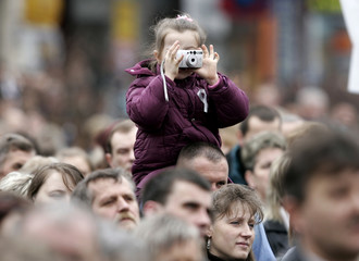 A little girl takes a picture during a mass for late Pope John Paul II on the main Square in Wadowice