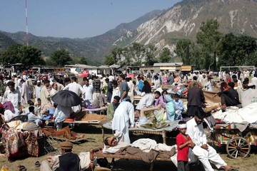Injured people from Kashmir gather at the university ground where they are taken to Islamabad by army helicopters