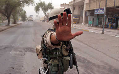 Iraqi soldier gestures to photographers near scene of suicide bomb attack in Baghdad.