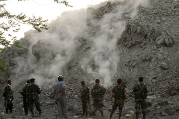 Philippine soldiers watch rocks tumbling down the slopes of Mayon volcano