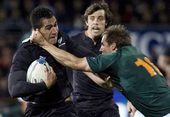 New Zealand's Muliaina is tackled by South Africa's James during rugby match in Dunedin