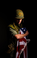 Distraught US marine (Vietnam War) holding the American flag.