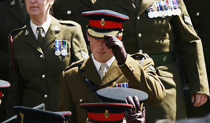 Britain's Prince Harry adjust his cap as he stands with soldiers representing all the units in the British Army 52nd Brigade after attending a memorial service at St.Giles Cathedral in Edinburgh, Scotland