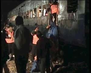 Rescue workers inspect the wreckage of a train in this TV grab in Shiba, near Panipat town, India