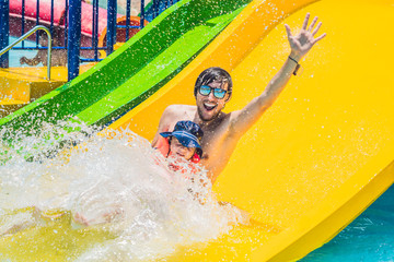 Foto op Aluminium Amusementspark Father and son on a water slide in the water park