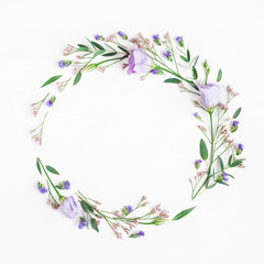 Flowers composition. Wreath made of pink flowers and eucalyptus branches on white background. Flat lay, top view