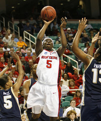 Rutgers University's Essence Carson shoots between the defense of George Washington University in Greensboro