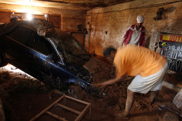 Man removes mud around his car in his garage after floods in Ghardaia south of Algiers
