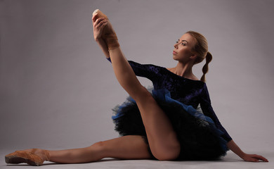 beautiful ballerina in blue outfit in studio sit on the floor and hold her leg