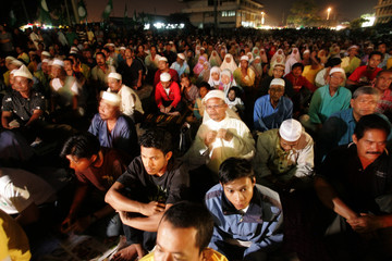 Malaysians listen during a election campaign rally in Kuala Terengganu