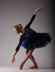 incredibly beautiful ballerina with perfect body in blue outfit posing. classical ballet