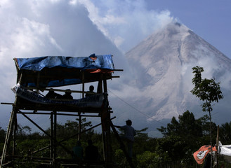 A villagers watch Mount Merapi volcano from a tower as its spews smoke in Tunggularum village near Indonesia city of Yogyakarta
