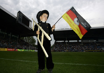 5 year old Julius, dressed as chimney sweeper, waves a German flag after the German national soccer team's friendly match against Luckenwalde in Mannheim