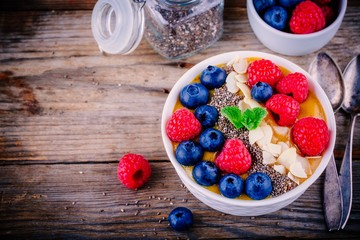 Mango smoothie bowl with raspberries, blueberries, chia seeds and almonds