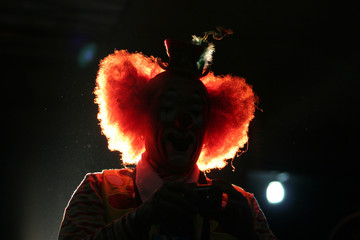 A clown is silhouetted as he watches a performance at an international clown convention in Mexico City