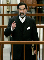 Former Iraqi President Saddam Hussein addresses the court of the Iraqi High Tribunal at the start of proceedings in Baghdad