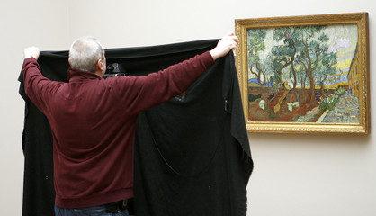 A photographer uses a black cloth as he takes a picture of 'The garden of St. Pauls hospital' by van Gogh at the Kunstmuseum Basel in Basel