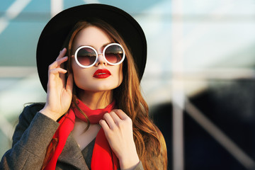 Outdoor close up portrait of young beautiful woman posing on street, looking up, aside. Model wearing stylish hat, round sunglasses, scarf. Female fashion concept. Sunset. Copy, empty space for text