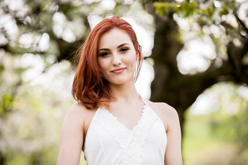 Gorgeous redhead woman in outdoor photo in sunny summer day. Beautiful girl in springtime